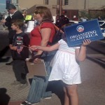 A young girl waves a sign supportive of Obama to protect herself from the sun and fan off the heat
