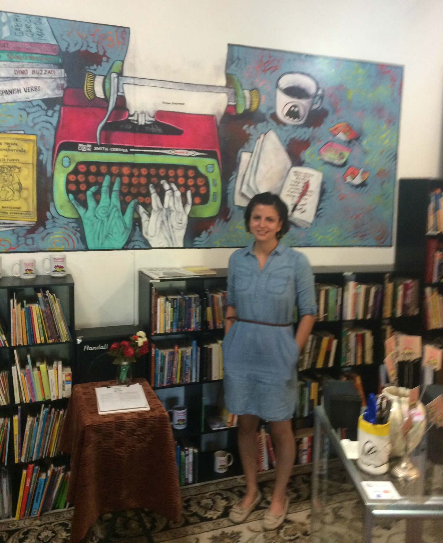 Palabras Libreria/Bookstore Founder and Director Rosie Magana in front of  Jeff Slim's mural.
